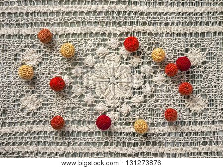Red, orange and yellow crochet beads on white vintage crochet lace. Cotton yarn for knitting, crochet. Crochet doily, crochet pattern on wooden background