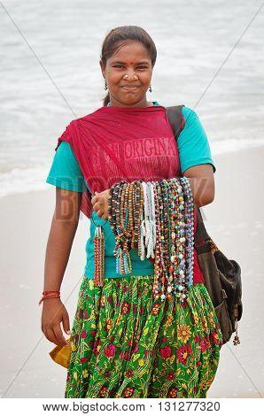 MAMALLAPURAM INDIA - OCT 11: Unidentified woman sells souvenirs on the beach on October 11 2014 in Mahabalipuram Tamil Nadu India.
