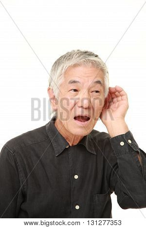 studio shot of senior Japanese man with hand behind ear listening closely on white background