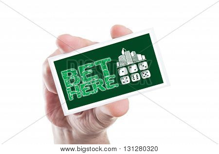 Hand Holding Bet Here Card As Online Betting Concept