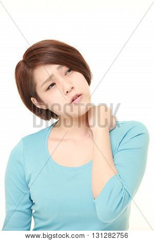 studio shot of young Japanese woman suffers from neck ache