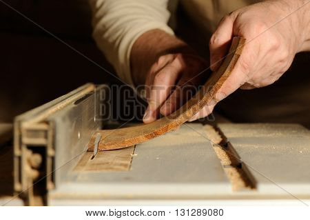Carpenter cutting curved piece of wood by wood cutter closeup