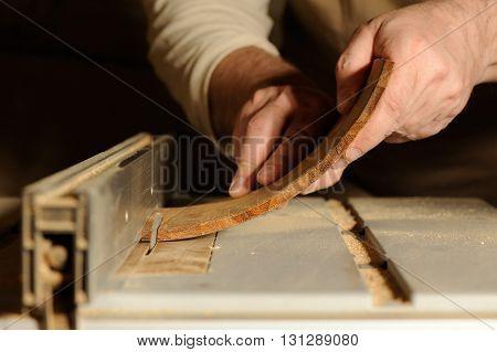 Carpenter cutting curved piece of wood by wood cutter closeup
