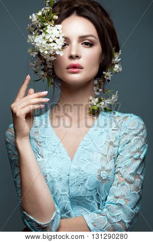 Beautiful brunette girl in blue dress with a gentle romantic make-up pink lips and flowers. The beauty of the face. Portrait shot in the studio.