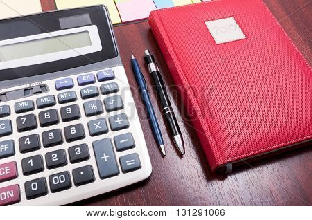 Wooden Desktop With Red Agenda And Calculator
