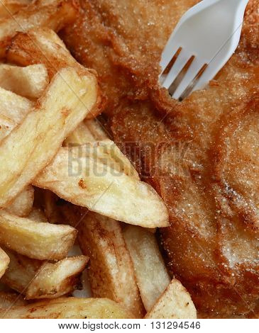 Closeup of freshly fried fish and chips with plastic fork