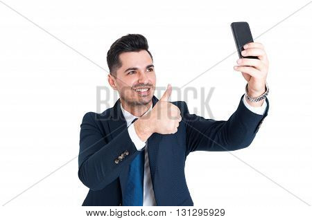 Happy businessman in clasic suit making a selfie and showing thumb up isolated on white background