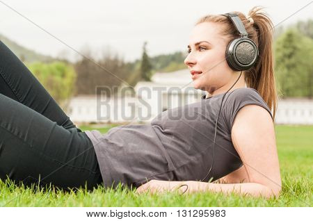 Young Woman Listening Music On Headphones While Lying On Grass