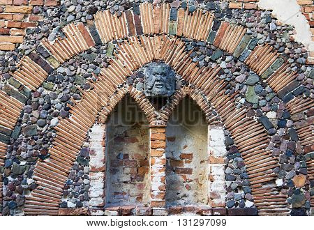 The art wall with the mascaron in Arkadia park in Poland. The Arkadia park is the known romantic English landscape garden in Poland. The wall fragment belong to the