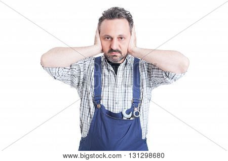 Young Attractive Mechanic Covering His Ears With Hands