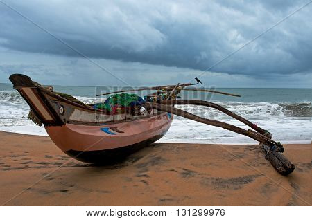 Ocean handmade wood fish boat on littoral. Cloudly sky in background.