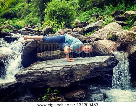 Vintage retro effect hipster style image of sporty fit woman doing yoga asana Eka Pada Koundinyasana 1 at tropical waterfall