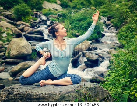 Vintage retro effect hipster style image of sporty fit woman doing yoga asana Eka pada rajakapotasana - one-legged king pigeon pose at tropical waterfall. Himachal Pradesh, India