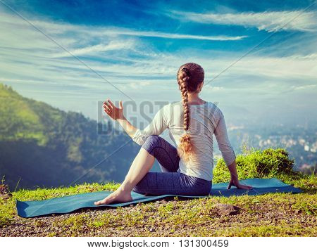 Vintage retro effect hipster style image of sporty fit woman practices yoga asana Parivrtta Marichyasana -  seated spinal twist outdoors in mountains in the  morning
