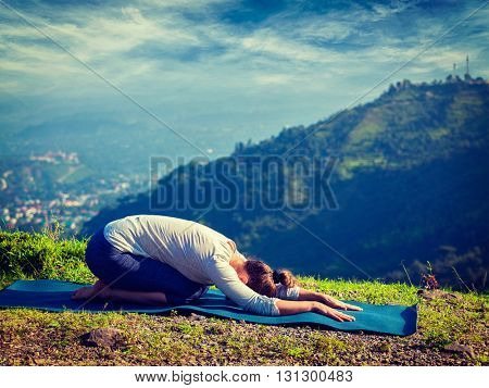 Vintage retro effect hipster style image of sporty fit woman practices yoga asana Balasana - child pose outdoors in mountains