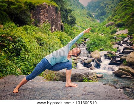 Vintage retro effect hipster style image of sproty fit woman practices yoga asana Utthita Parsvakonasana -  extended side angle pose outdoors at water