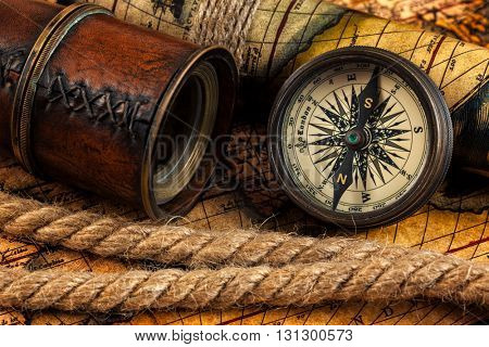 Travel geography navigation concept background - old vintage retro compass on ancient world map with spyglass