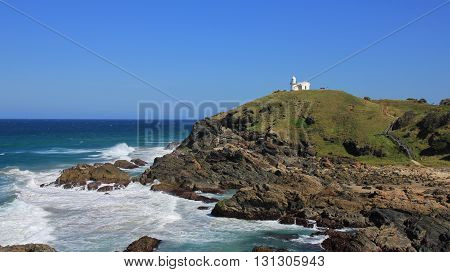 Coast scene in Port Macquarie Australia. Small lighthouse on top of a hill. Turquoise pacific.