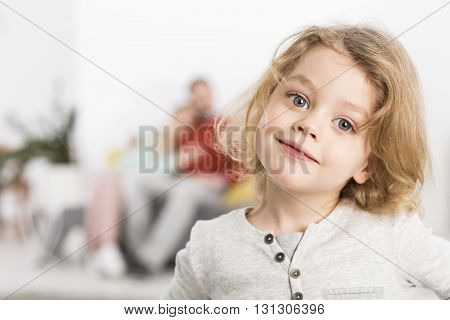 Optimistic portrait of a little blonde boy with a cheery smile with his parents cuddling in a very blurred background