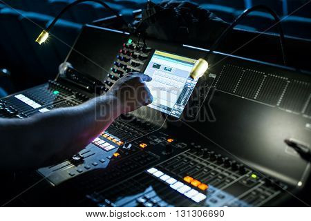 Large modern show sound controller with lighted screen operators hand and ajusted presets - close up photo