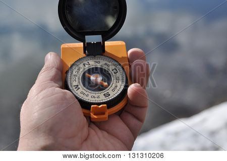 Magnetic compass in the black case on an orange ground with mirror cover to be in the hands of man.