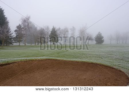 Golf course sand bunker on a cold and misty day