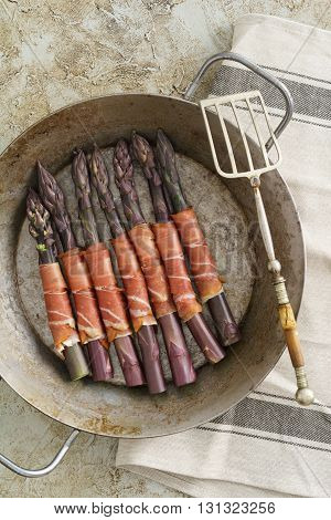 Purple asparagus wrapped with gammon in a skillet