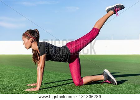Active Asian young adult doing bodyweight glute and leg exercises on outdoor grass. Fitness woman doing donkey kick exercise for glutes strength training, butt toning and body core health.