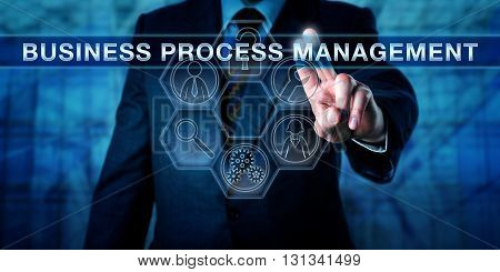 Male executive is pressing BUSINESS PROCESS MANAGEMENT on an interactive touch screen display. Business metaphor and technology concept for a strategic focus on corporate performance as an asset.
