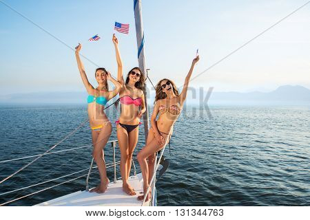 Smiling girls with american flags. Sexy women standing on yacht. Heading for America. Don't be bored.