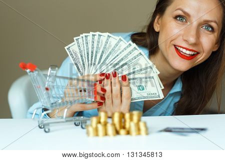 Young smiling woman holding cash and on the table are coins credit card and the shopping cart - online shopping concept
