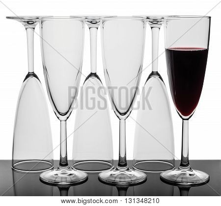 Set of six wine glasses. Glasses standing in a row three glasses upside down one glass with red wine. Isolated on the white background.