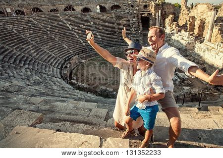 Funny family take a self photo in amphitheatre building