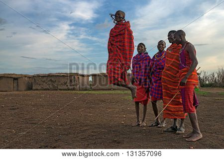 MAASAI VILLAGE KENYA - JANUARY 2 2015: Tourists visit maasai village near Maasai Mara. Watching traditions of local tribes is one of the most popular attraction for tourists who come to Kenya.