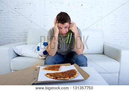 young supporter man with ball pizza and beer bottle watching football game on television sitting at home couch covering his eyes sad dejected and disappointed for failure or defeat