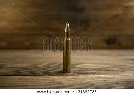 Closeup photo of riffle bullet on old wooden desk
