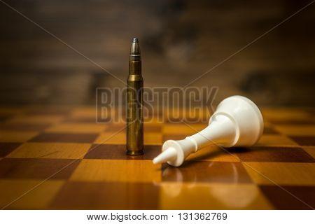 Closeup photo of bullet wins chess game. Concept of gun power
