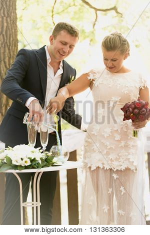 Toned photo of beautiful bride and groom strewing sand in glasses at wedding ceremony