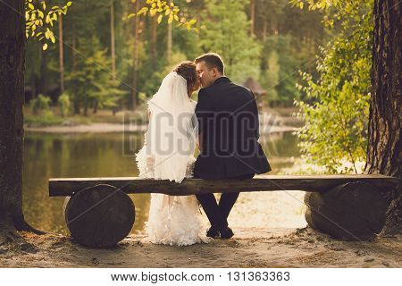 Rear view on beautiful newlyweds kissing on bench at river