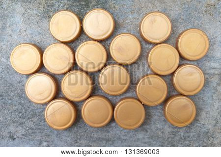 Recycled gold plastic bottle caps on stone