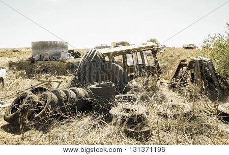 Old tires and car chassis with junk pile in Western Australian farmland in aged photo.