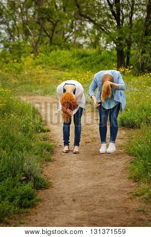Best friends forever. Girlfriends corrected her hair in a park. BFF. Close friends. Gentle friendship.