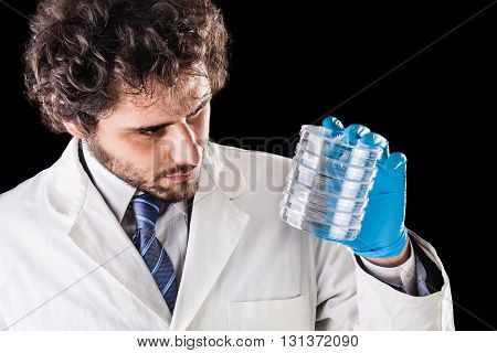 Holding A Stack Of Petri Dishes