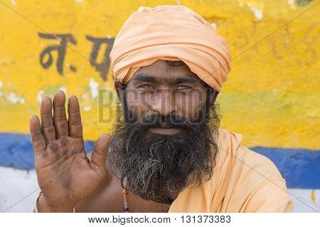 PUSHKAR INDIA - OCTOBER 24 2014: Unidentified Indian sadhu - holy man sits on the ghat along the sacred Sarovar lake. Pushkar - famous worship place in India