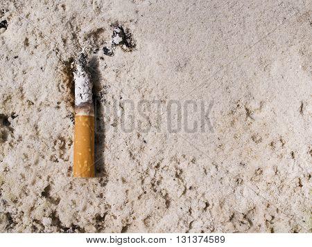 A cigarette in sand ashtray for health concept.