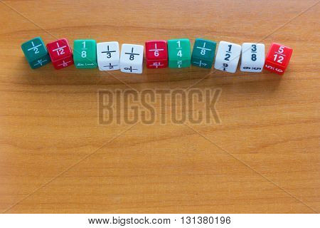 Multicolored fraction dices line up on wooden table with room for copyspace at bottom of frame