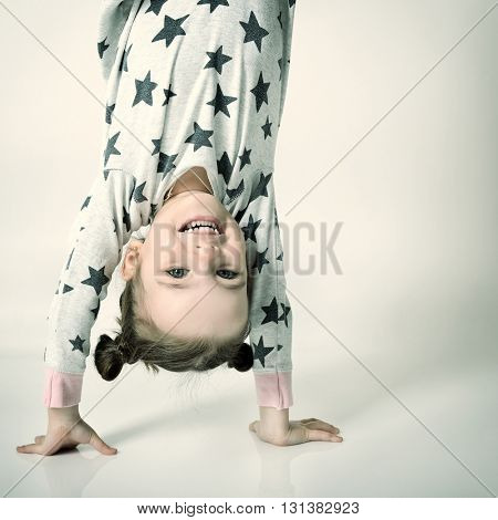 Upside down funny portrait of little happy sleepless girl in pajamas.