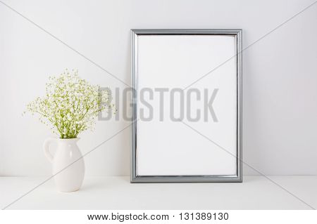 Frame mockup with white tender flowers. Frame mockup. Poster Mockup. Styled mockup. Product mockup. White frame mockup. Design Mockup. Silver frame mockup.