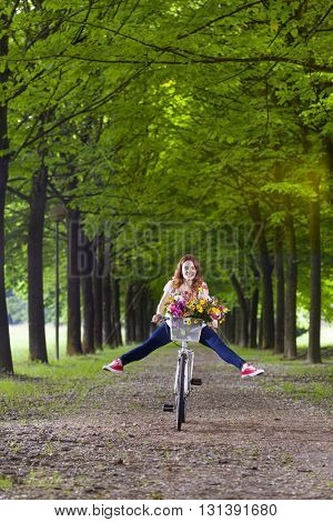 Young woman having fun - riding a bike at the park with her legs in the air