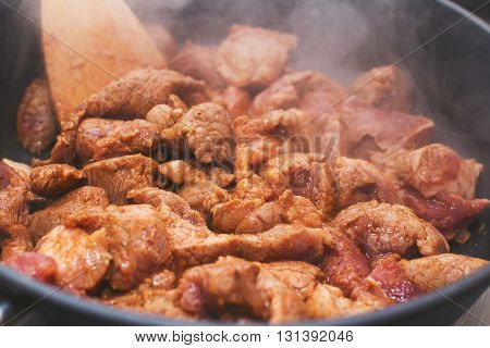 Pork fried in a pan with wooden spatula